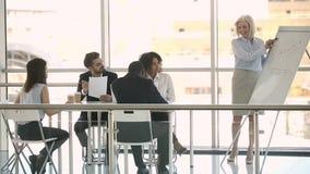 Μέσος ηλικίας εκπαιδευτής επιχειρηματιών που παρουσιάζει για το whiteboard στην αίθουσα συνεδριάσεων απόθεμα βίντεο