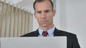 Μέσος ηλικίας επιχειρηματίας που εργάζεται στο lap-top στην αρχή φιλμ μικρού μήκους