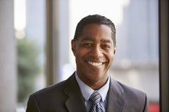 Μέσος ηλικίας μαύρος επιχειρηματίας που χαμογελά στη κάμερα Στοκ εικόνα με δικαίωμα ελεύθερης χρήσης