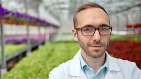 Μέσος κινηματογραφήσεων σε πρώτο πλάνο εργαζόμενος γεωργίας επιστημόνων αρσενικών πορτρέτου χαμογελώντας που φορά τα γυαλιά που ε φιλμ μικρού μήκους