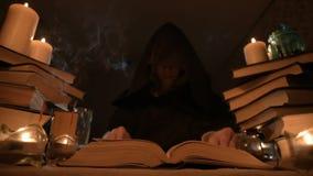 Μέσος μάγος κοριτσιών κινηματογραφήσεων σε πρώτο πλάνο σε μια κουκούλα σε ένα σκοτεινό δωμάτιο με το φως ιστιοφόρου και την έρευν φιλμ μικρού μήκους
