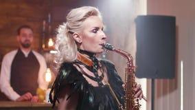 Μέσος πυροβολισμός ενός θηλυκού μουσικού που εκτελεί μια σύνθεση σε ένα saxophone φιλμ μικρού μήκους