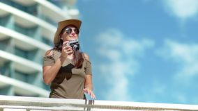 Μέσος πυροβολισμός που χαμογελά το θηλυκό επαγγελματικό φωτογράφο που κάνει τη φωτογραφία που χρησιμοποιεί τη κάμερα στο πεζούλι  απόθεμα βίντεο
