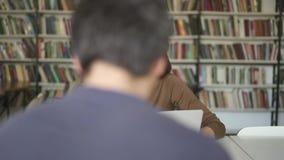 Μέσος πυροβολισμός της αρσενικής συνεδρίασης σπουδαστών στην εκμετάλλευση βιβλιοθηκών ένα κενό που εξετάζει το lap-top απόθεμα βίντεο