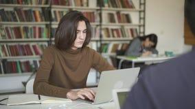 Μέσος πυροβολισμός της αρσενικής συνεδρίασης σπουδαστών στη δακτυλογράφηση βιβλιοθηκών το lap-top φιλμ μικρού μήκους