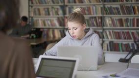 Μέσος πυροβολισμός της γυναίκας σπουδαστή που κάνει τις σημειώσεις καθμένος στη βιβλιοθήκη απόθεμα βίντεο