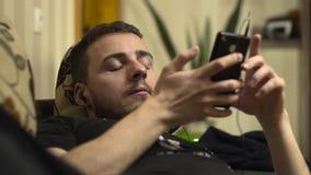 Μέσος πυροβολισμός της μουσικής ακούσματος ατόμων στο κινητό τηλέφωνο στο κρεβάτι φιλμ μικρού μήκους