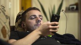 Μέσος πυροβολισμός της μουσικής ακούσματος νεαρών άνδρων στο κινητό τηλέφωνο στο κρεβάτι απόθεμα βίντεο
