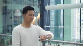 Μέσος πυροβολισμός του ασιατικού αρσενικού που περπατά και που στο smartwatch στο αριστερό φιλμ μικρού μήκους