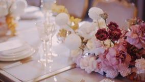 Μέσος πυροβολισμός των τριαντάφυλλων, των παπαρουνών και των γαρίφαλων στις γαμήλιες διακοσμήσεις φιλμ μικρού μήκους