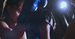 Μέσος πυροβολισμός των όμορφων γαντιών πυγμαχίας εστίασης ταχύτητας απεργίας treneruemsya μπόξερ γυναικών ικανότητας με ένα λεωφο απόθεμα βίντεο