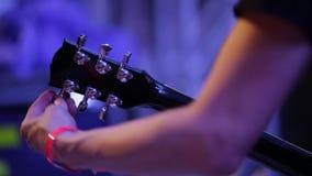 Μέσος πυροβολισμός του βραχίονα του μουσικού που συντονίζει τα ηλεκτρικά παρασκήνια κιθάρων στη συναυλία φιλμ μικρού μήκους