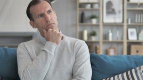 Μέσο ηλικίας άτομο που σκέφτεται τη νέα ιδέα καθμένος στον καναπέ στο δημιουργικό γραφείο απόθεμα βίντεο