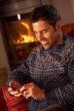 Μέσο ηλικίας άτομο που χρησιμοποιεί MP3 το φορέα από την άνετη πυρκαγιά κούτσουρων Στοκ Εικόνα