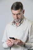 Μέσο ηλικίας άτομο που εξετάζει το τηλέφωνό του Στοκ φωτογραφία με δικαίωμα ελεύθερης χρήσης