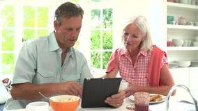 Μέσο ηλικίας ζεύγος που εξετάζει την ψηφιακή ταμπλέτα πέρα από το πρόγευμα απόθεμα βίντεο