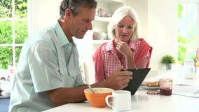 Μέσο ηλικίας ζεύγος που εξετάζει την ψηφιακή ταμπλέτα πέρα από το πρόγευμα φιλμ μικρού μήκους