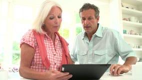Μέσο ηλικίας ζεύγος που εξετάζει την ψηφιακή ταμπλέτα που έχει το επιχείρημα απόθεμα βίντεο