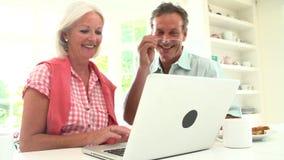Μέσο ηλικίας ζεύγος που εξετάζει το lap-top πέρα από το πρόγευμα φιλμ μικρού μήκους