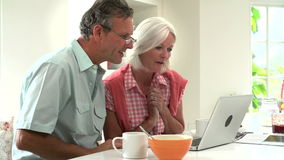 Μέσο ηλικίας ζεύγος που εξετάζει το lap-top πέρα από το πρόγευμα απόθεμα βίντεο