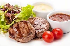 Μέσο μπριζολών βόειου κρέατος σχαρών που ψήνεται στη σχάρα με τις άσπρες και κόκκινες σάλτσες Στοκ εικόνα με δικαίωμα ελεύθερης χρήσης