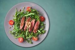 Μέσο μπριζόλας βόειου κρέατος, σαλάτα Ruccola με τις ντομάτες και τα ξύλα καρυδιάς, γκρίζο πιάτο στοκ φωτογραφίες με δικαίωμα ελεύθερης χρήσης