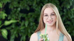 Μέσο πορτρέτο κινηματογραφήσεων σε πρώτο πλάνο του χαμογελώντας νέου κοριτσιού με το ποτό ανανέωσης στη θερινή ημέρα απόθεμα βίντεο