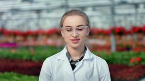 Μέσο πορτρέτο κινηματογραφήσεων σε πρώτο πλάνο του όμορφου χαμογελώντας θηλυκού γεωργικού μηχανικού σε ομοιόμορφο φιλμ μικρού μήκους