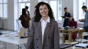 Μέσο πορτρέτο της νέας καυκάσιας επιχειρησιακής γυναίκας με τη σγουρή τρίχα, επίσημο χαμόγελο κοστουμιών ευτυχές στη κάμερα στο σ απόθεμα βίντεο
