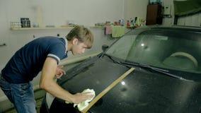 Μέσο πυροβοληθε'ν μαύρο αυτοκίνητο στιλβωτικής ουσίας εργαζομένων με τα ειδικά εργαλεία φιλμ μικρού μήκους