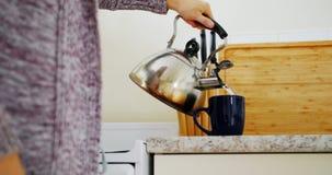 Μέσο τμήμα της γυναίκας που προετοιμάζει τον καφέ στην κουζίνα φιλμ μικρού μήκους