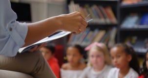 Μέσο τμήμα της θηλυκής διδασκαλίας δασκάλων schoolkids στη σχολική βιβλιοθήκη 4k φιλμ μικρού μήκους