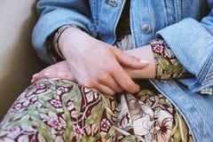 Μέσο τμήμα της νέας γυναίκας που φορά το σακάκι τζιν πέρα από το θερινό φόρεμα με το floral σχέδιο στοκ εικόνα