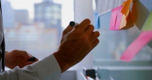 Μέσο τμήμα της νέας καυκάσιας αρσενικής εκτελεστικής εργασίας στην κολλώδη σημείωση σε ένα σύγχρονο γραφείο 4k φιλμ μικρού μήκους