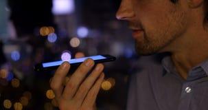 Μέσο τμήμα της νέας καυκάσιας αρσενικής εκτελεστικής ομιλίας στο κινητό τηλέφωνο σε ένα σύγχρονο γραφείο 4k φιλμ μικρού μήκους
