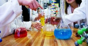 Μέσο τμήμα της πειραματιμένος χημικής ουσίας schoolkids στο εργαστήριο 4k φιλμ μικρού μήκους