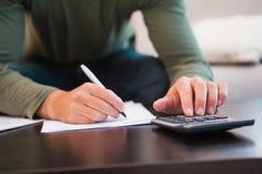 Μέσο τμήμα του ατόμου που παίρνει τις σημειώσεις και που χρησιμοποιεί τον υπολογιστή Στοκ Φωτογραφία