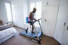 Μέσο τμήμα του ατόμου που χρησιμοποιεί το έξυπνο ρολόι ασκώντας treadmill Στοκ φωτογραφία με δικαίωμα ελεύθερης χρήσης