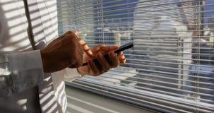Μέσο τμήμα του νέου καυκάσιου αρσενικού ανώτερου υπαλλήλου που χρησιμοποιεί το κινητό τηλέφωνο κοντά στο παράθυρο στο σύγχρονο γρ απόθεμα βίντεο