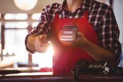 Μέσο τμήμα του σερβιτόρου που παρουσιάζει μηχανή πιστωτικών καρτών στοκ εικόνα