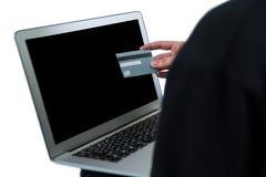 Μέσο τμήμα του χάκερ που χρησιμοποιεί το lap-top και την πιστωτική κάρτα Στοκ Φωτογραφία