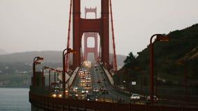 Μέσο χρονικό σφάλμα που πυροβολείται των φωτεινών σηματοδοτών αυτοκινήτων στην εικονική χρυσή γέφυρα πυλών στο θερινό ηλιοβασίλεμ απόθεμα βίντεο