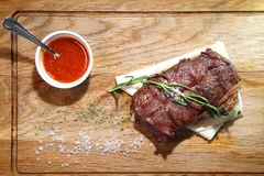 Μέσο ψητό μπριζόλας σε έναν ξύλινο πίνακα με τη σάλτσα και το άλας Στοκ Φωτογραφίες