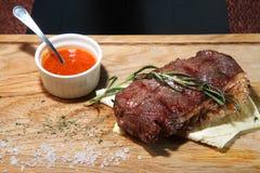 Μέσο ψητό τοπ λεπίδων μπριζόλας σε έναν ξύλινο πίνακα με τη σάλτσα και το άλας Στοκ Εικόνα