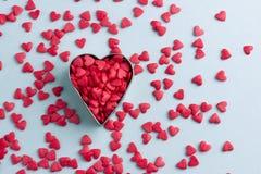 Μέταλλο και κόκκινες καρδιές στο μπλε υπόβαθρο χαρτονιού ή εγγράφου στοκ εικόνες