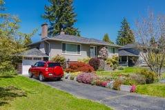 Μέτριο κατοικημένο σπίτι το κόκκινο αυτοκίνητο που σταθμεύουν με driveway στο μέτωπο Οικογενειακό σπίτι με τα ανθίζοντας λουλούδι στοκ φωτογραφία