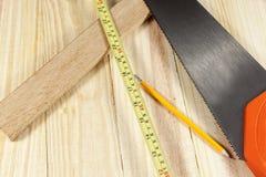 Μέτρο πριονιών και ταινιών χεριών που βάζει σε ένα επιβιβασμένο ξύλινο πάτωμα Στοκ φωτογραφίες με δικαίωμα ελεύθερης χρήσης