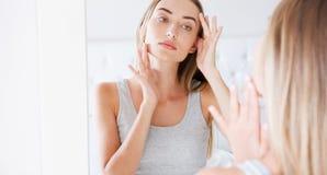 Μέτωπο νέων κοριτσιών του καθρέφτη στην κρεβατοκάμαρα που βάζει την κρέμα στο πρόσωπό της στοκ εικόνες