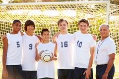 Μέλη της αρσενικής ομάδας ποδοσφαίρου γυμνασίου με το λεωφορείο στοκ φωτογραφίες