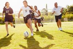 Μέλη της θηλυκής παίζοντας αντιστοιχίας ποδοσφαίρου γυμνασίου Στοκ Εικόνα